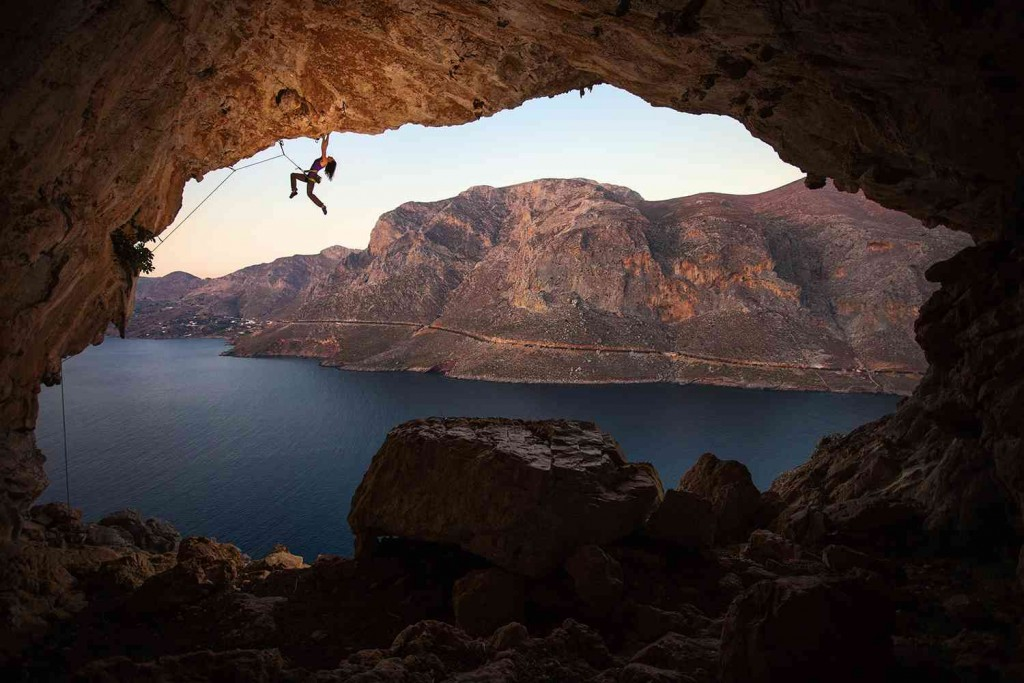 female rock climber hanging off cliff