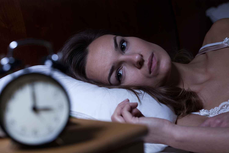 depressed woman staring at clock