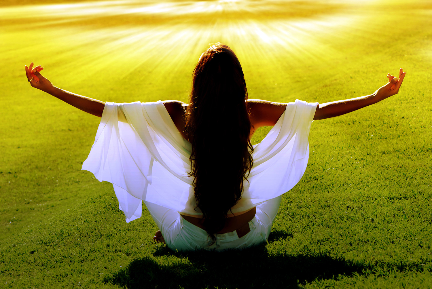woman meditating in field with solar beams
