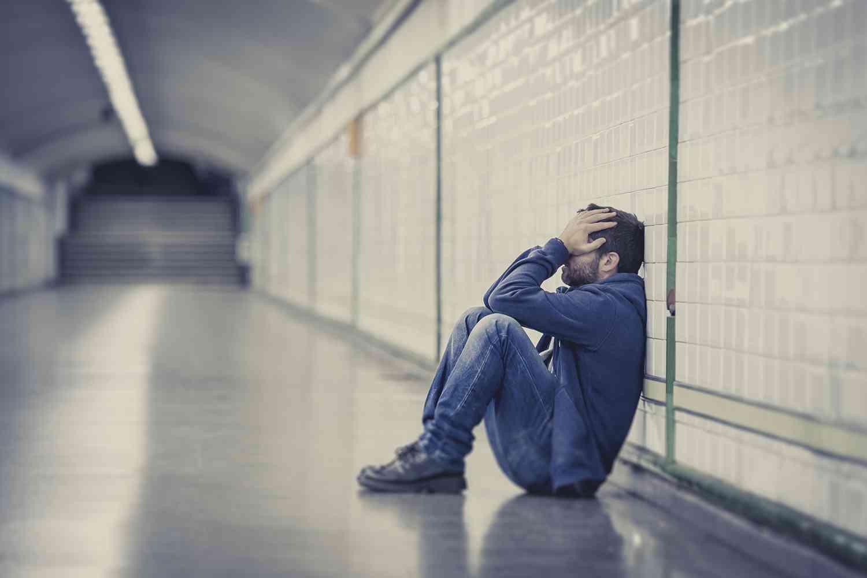 man sitting in tunnel depressed